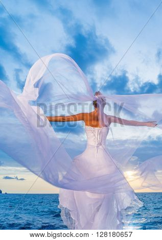 bride on a tropical beach with the sunset in the background