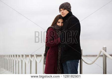 Happy young couple in love on the pier. Male and female fashion model outdoor. Young man and woman embracing