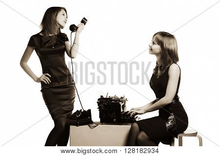 Two young fashion woman with a vintage typewriter and retro phone
