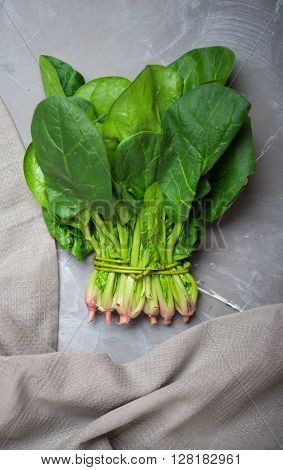 Fresh spinach on a gray stone background