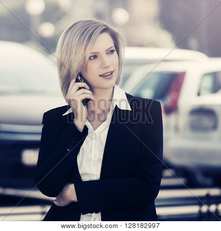 Young business woman calling on the cell phone on city street. Female blond fashion model in black jacket outdoor