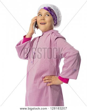Little girl in traditional muslim clothes with mobile phones isolated