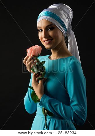 Young muslim woman in blue dress with rose flower