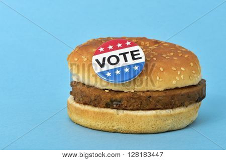 a pin button with the text vote for the the United States election on a hamburger, on a blue background