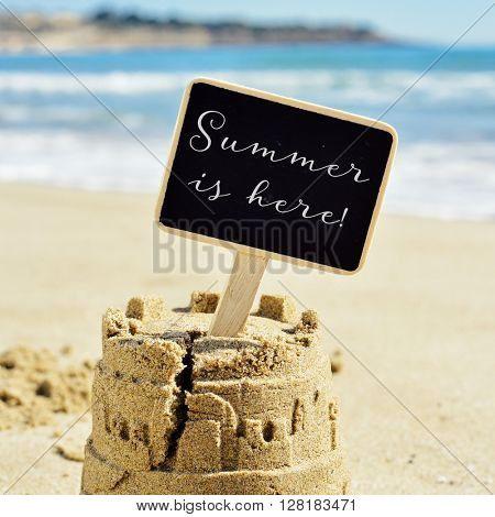 closeup of a sandcastle on the sand of a beach topped with a black signboard with the text summer is here written in it