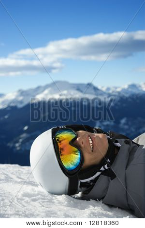 Caucasian teenage boy snowboarder wearing helmet and goggles, smiling, looking at viewer, lying in snow on mountain with mountain landscape in background Whistler, British Columbia, Canada.