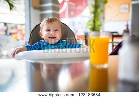 Baby boy eating lunch on the high chair