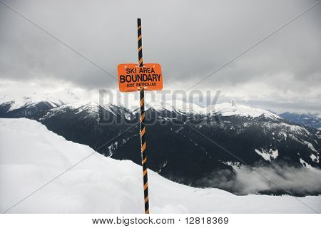 Ski area trail boundary sign with mountain landscape in background in Whistler, British Columbia, Canada.