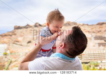 Happy smiling baby boy held up by his father on holidays