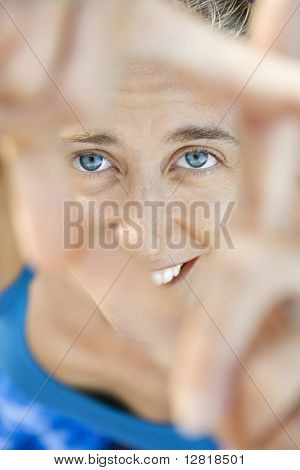 Close-up of Caucasian mid-adult woman smiling and looking at viewer through framed fingers.