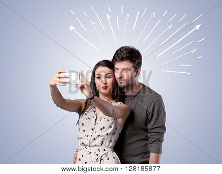 A cheerful young couple taking selfie photo with mobile phone and white lines and arrows pointing to the sky above them concept