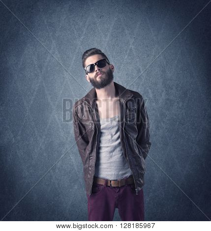 A handsome fashion model with beard standing in front of fancy background and making funny faces while using a vintage camera concept