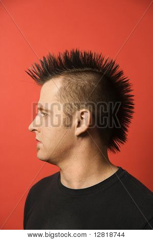 Profile portrait of Caucasian man with spiked mohawk against orange background.