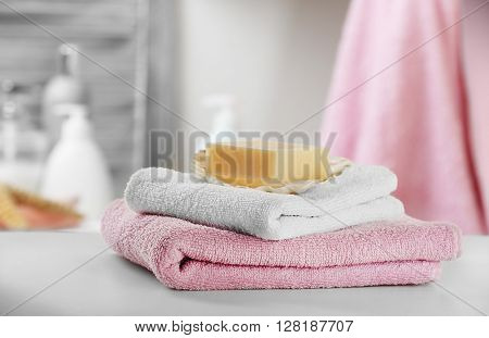 Soap with towels on bathroom table, close up