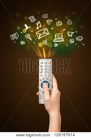 Hand holding a remote control, social media icons coming out of it