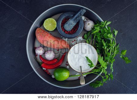 Ingredients to prepare Thai coconut creamy soup. Healthy and fresh vegetables on stone background.