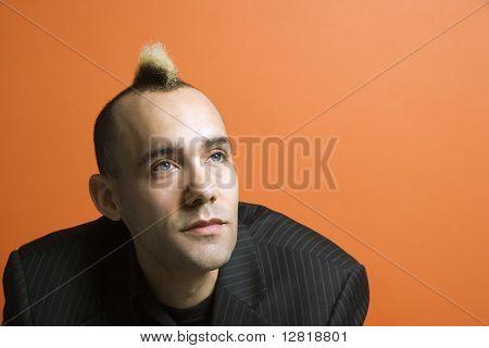Caucasian man in suit with mohawk against orange background.
