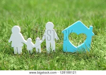 Cutout figurine of a family and house on green grass background