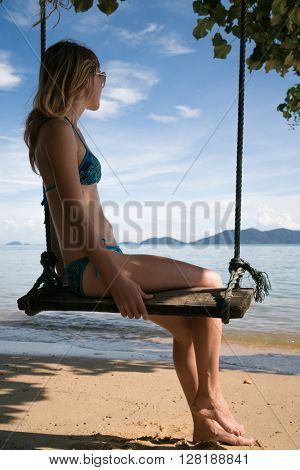 Young lady sitting on a swing on a tropical beach