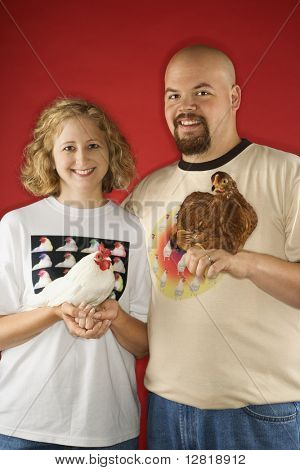 Caucasian mid-adult man and woman holding chickens.