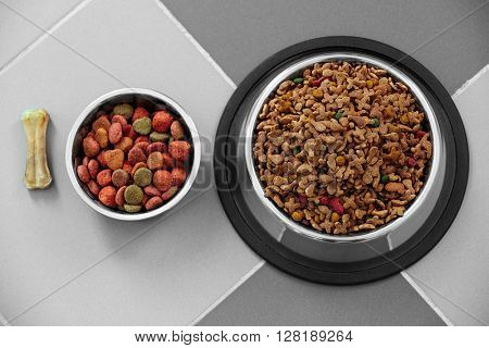 Pet food in  metal bowls on a floor.