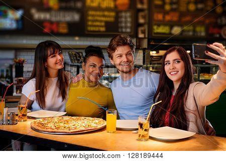 Cheerful multiracial friends taking selfie in pizzeria.