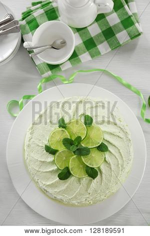 Delicious creamy lime cake on wooden table closeup