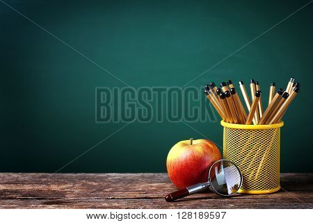 Set of pencils in metal holder, magnifier and apple on blackboard background