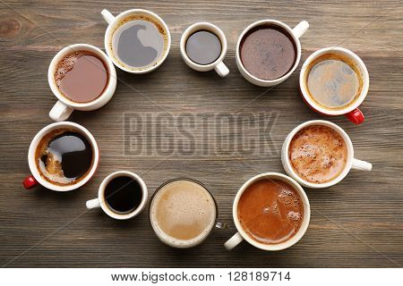 Different cups of coffee on wooden table, top view