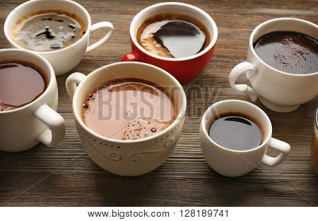 Different cups of coffee on wooden background