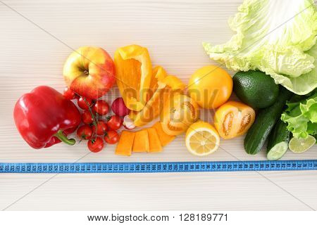 Fresh fruits and vegetables with measuring tape on wooden table, top view