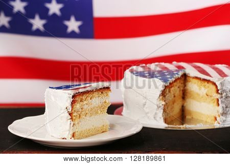 Piece of American flag cake, on black wooden table.