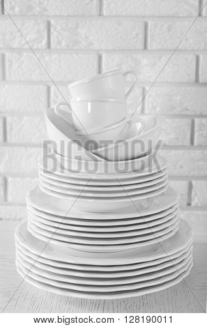 Stacked white clean plates and cups on  white table