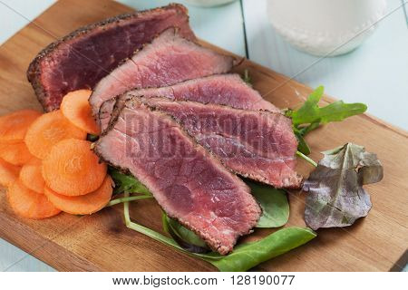 Rare beef steak, cut in slices, with carrot and green salad