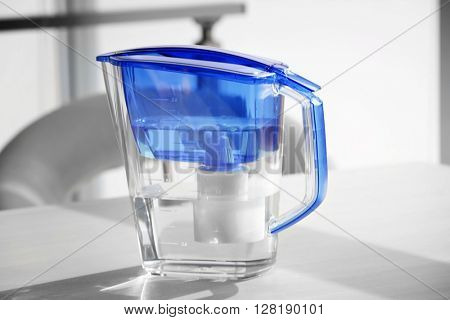 Water filter jug on light wooden table