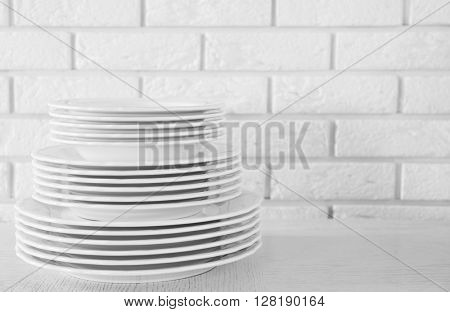 Stacked white dishes on  white table.