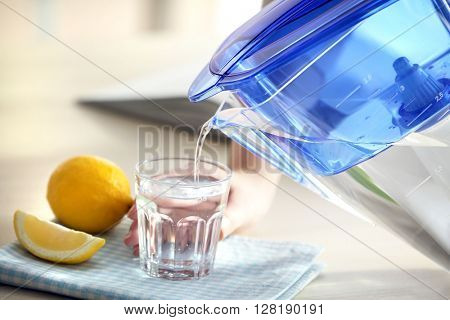 Pouring water from filter jug into glass in the kitchen