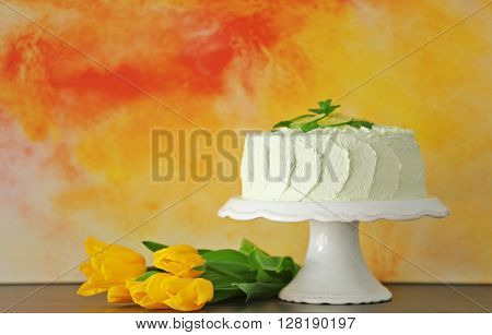 Big lime cake on a white stand beside light blue wall