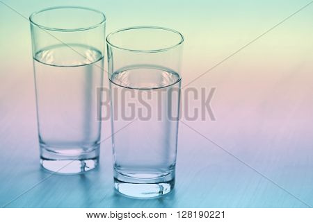 Two glasses of pure water on light wooden table