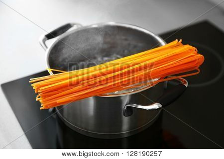 Pasta and boiling saucepan on electric stove in the kitchen