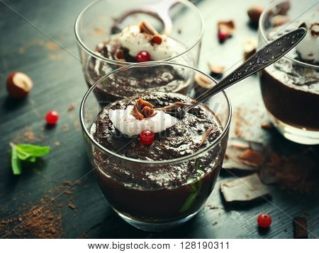 Glass cups of chocolate dessert with frothed milk and cranberries on black wooden table