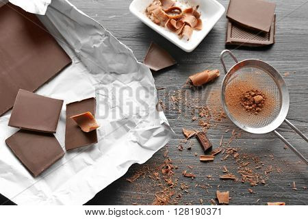 Pieces of chocolate with strainer on black wooden background