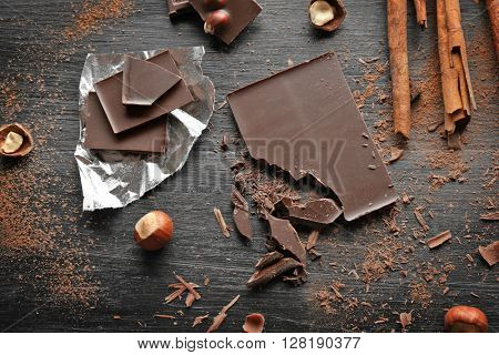 Pieces of chocolate with hazelnuts, cinnamon on black wooden background