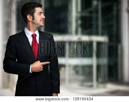 Smiling businessman pointing his finger to the copyspace