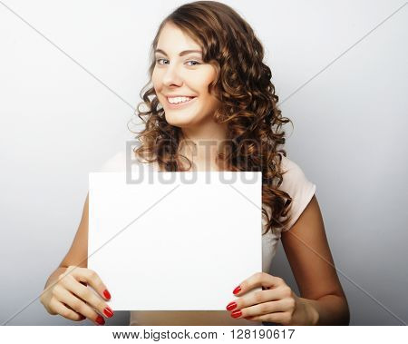 Smiling young casual style woman showing blank signboard