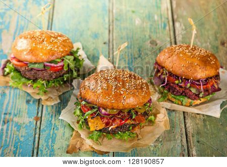 Close-up of home made tasty burgers on wooden table.