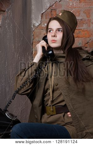 Woman in Russian military uniform speaks on phone. Female soldier during the second world war.