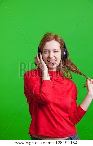 Woman listening music on headphones, green background