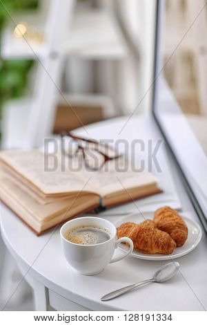 White cup of the coffee and an open book on the table  in a light room..
