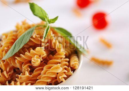 Fresh uncooked pasta in bowl closeup